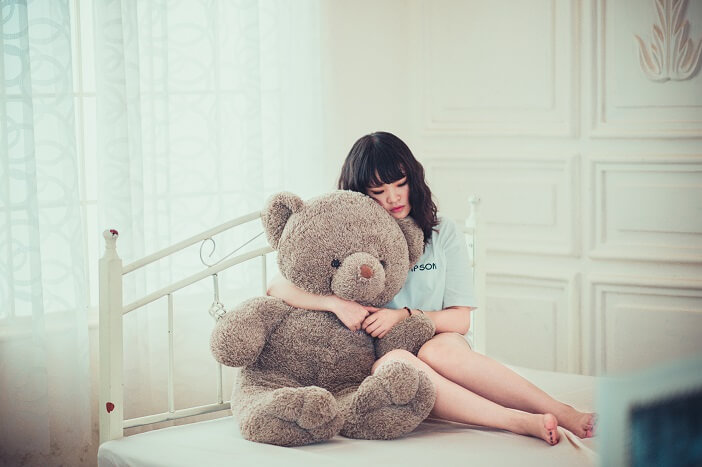 A girl holding on to a teddy bear and missing her better half-Illustration of 'When you miss him'